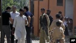 巴基斯坦警方星期一在本拉登被擊斃的住所外面監視記者