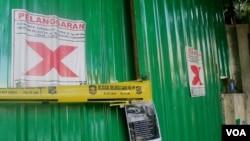 Segel dan tanda pelanggaran Perda dipasang di pagar seng jalan Mawar 10 Surabaya. (VOA/Petrus Riski)