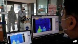 Sebuah pusat kebugaran di Seoul, Korea Selatan mendeteksi para pengunjungnya dengan layar monitor pengukur suhu tubuh, 25 Februari 2020.
