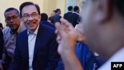Malaysian Opposition leader Anwar Ibrahim listens (2nd L) to his friend during a break at the federal court in Putrajaya, Oct. 30, 2014.
