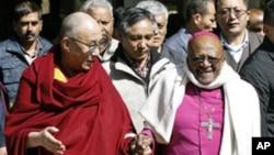 Tibetan spiritual leader Dalai Lama (L) and South African Archbishop and Nobel Laureate Desmond Tutu walk visiting a Tibetan temple in Dharamsala, India, February 10, 2012.