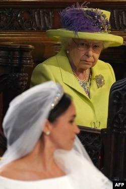 Rainha Elizabeth olha para Meghan Markle no dia do casamento com o príncipe Harry em Maio de 2018