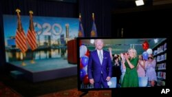 Democratic presidential candidate former Vice President Joe Biden is seen in a video feed from Delaware as he reacts with his wife Jill Biden and his grandchildren at his side, after winning the votes to become the Democratic Party's 2020 nominee for Pres