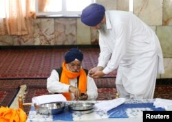 An Afghan Sikh (R) receives karah prasad, a sweet pudding offering given out to a congregation at the end of prayer, inside a Gurudwara, or a Sikh temple, during a religious ceremony in Kabul, Afghanistan, June 8, 2016.