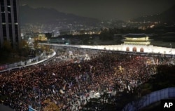 FILE - South Korean protesters march toward the presidential house during a rally calling for South Korean President Park Geun-hye to step down in Seoul, South Korea, Nov. 19, 2016.