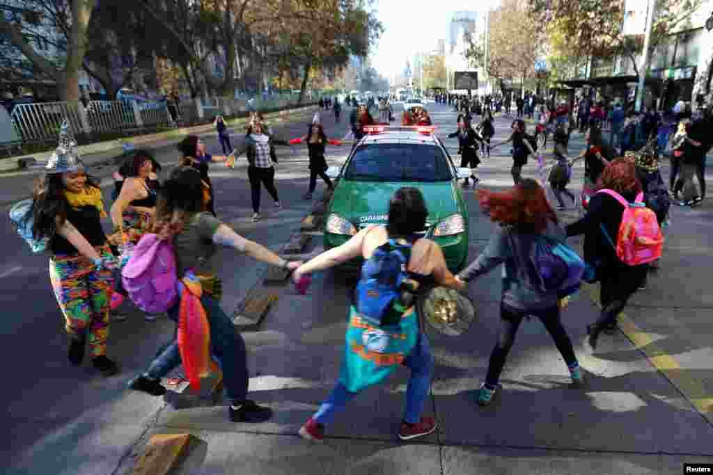 칠레 산티아고에서 성차별과 성폭력 근절을 촉구하며 행진하던 시위대가 경찰차를 둘러싸고 있다.