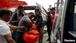 Para petugas membawa seorang korban dari pesawat kecil milik maskapai penerbangan Summit Air yang menabrak helicopter yang terparkir di Bandara Lukla, sebelum membawa korban ke sebuah rumah sakit di Kathmandu, Nepal, 14 April 2019.