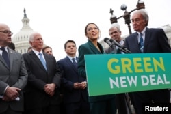 FILE - U.S. Representative Alexandria Ocasio-Cortez (D-NY) and Senator Ed Markey (D-MA) hold a news conference for their proposed Green New Deal to achieve net-zero greenhouse gas emissions in 10 years, at the U.S. Capitol in Washington, Feb. 7, 2019.