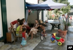 FILE - Women sit and talk while children play at a Gypsy camp in Rome, Aug. 6, 2008.