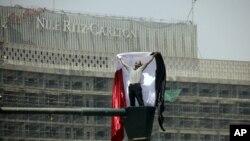 អ្នកតវ៉ាអេហ្ស៊ីបម្នាក់លើកទង់ជាតិហើយស្រែកនៅកន្លែងតវ៉ាមួយនៅទីលាន Tahrir Square ក្នុងរដ្ឋធានីឡឺគែរ ប្រទេសអេហ្ស៊ីប ថ្ងៃទី៤ ឧសភា ២០១២។