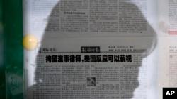资料照片:一名女子在北京的某处报纸橱窗阅读《环球时报》。该报的文章呼吁忽视美国对中国打压维权律师的批评。(2015年7月14日)