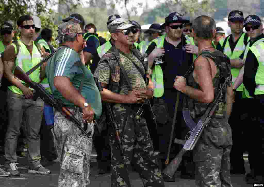Pro-Russian separatists stand near Dutch and Australian forensic experts preparing to continue recovery work near the village of Rozsypne, in the Donetsk region, Aug. 4, 2014.