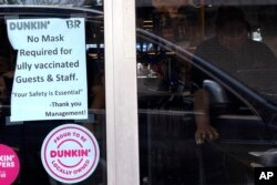 FILE - A COVID advisory is displayed at a Dunkin' store in Arlington Heights, Illinois, June 30, 2021.