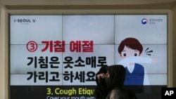 People wearing face masks pass by an electric screen about precautions against the illness COVID-19 in Seoul, South Korea, Tuesday, Feb. 18, 2020.