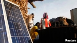 FILE - A youth charges batteries with solar panels at a makeshift shop in a camp for internally displaced persons at a United Nations base in South Sudan, June 17, 2014.