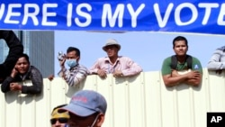 """Cambodian workers look through a partition of a construction site below a banner which reads """"Where is my vote"""" as supporters of opposition Cambodia National Rescue Party gather in Phnom Penh, Cambodia, Saturday, Sept. 7, 2013."""