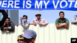 "Cambodian workers look through a partition of a construction site below a banner which reads ""Where is my vote"" as supporters of opposition Cambodia National Rescue Party gather in Phnom Penh, file photo."