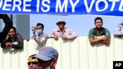 """Cambodian workers look through a partition of a construction site below a banner which reads """"Where is my vote"""" as supporters of opposition Cambodia National Rescue Party gather in Phnom Penh, file photo."""
