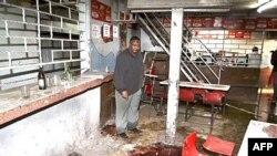 Người chủ quán xem xét vết máu trên sàn nhà sau khi quán bị ném lựu đạn