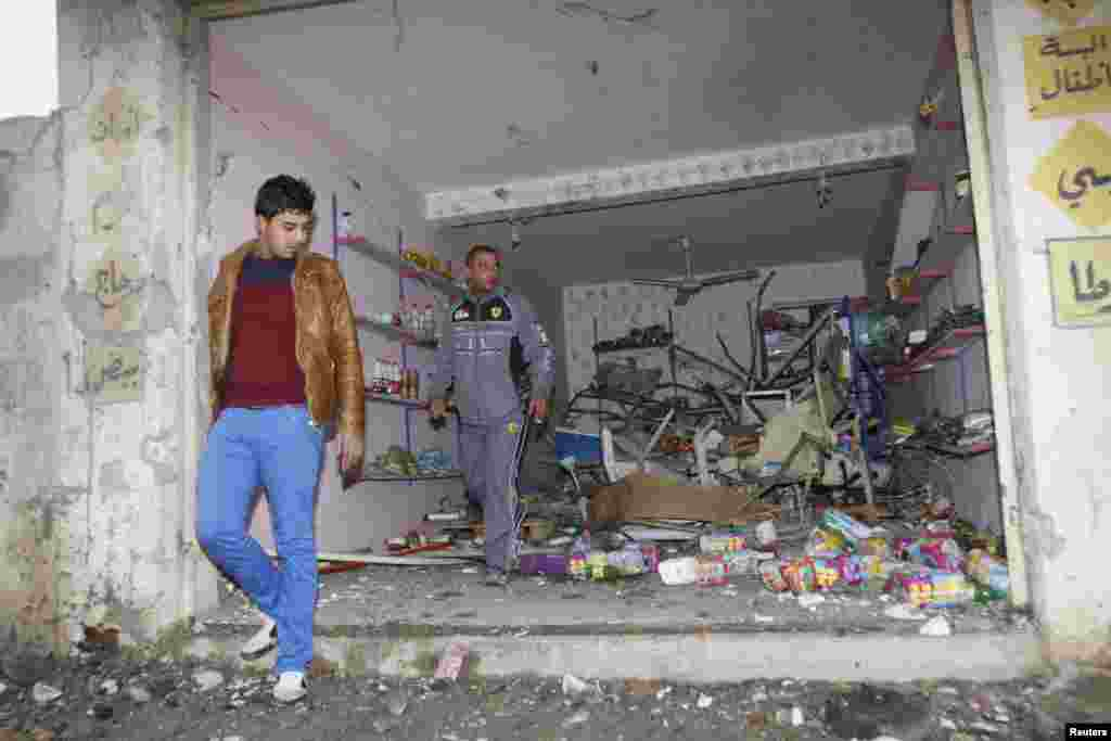People gather at the site of a car bomb attack in Kirkuk, north of Baghdad, Jan. 15, 2014.