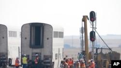 Workers examine a train car, Sept. 27, 2021, from an Amtrak train that derailed Saturday, near Joplin, Mont.