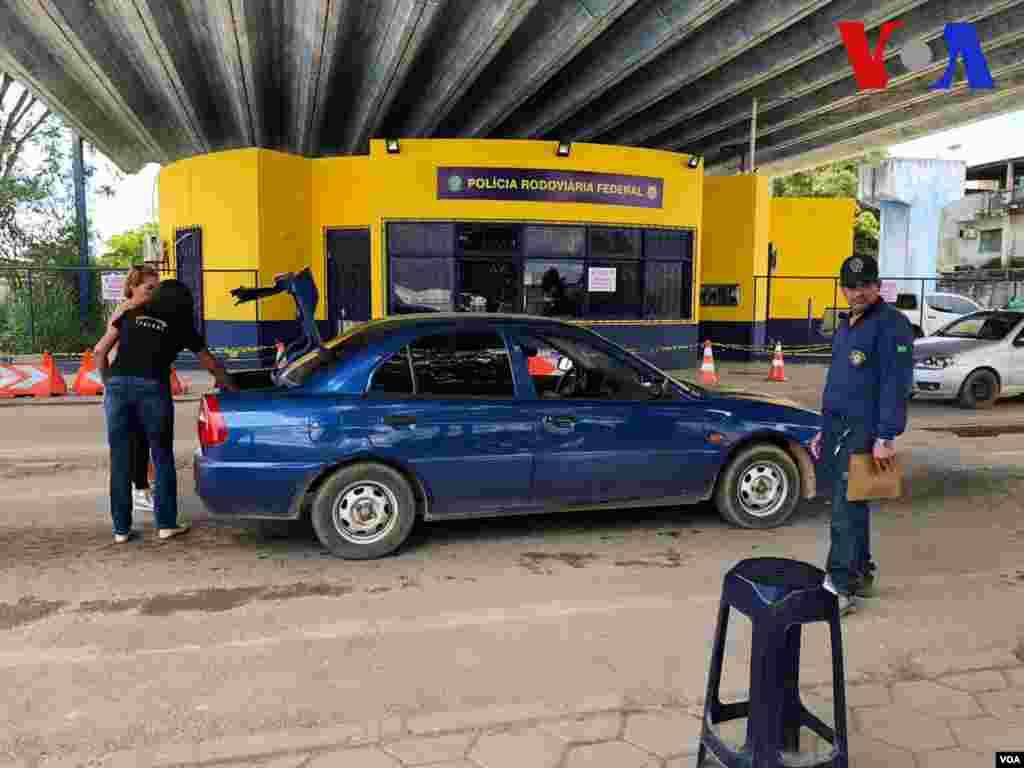 Policía local realiza un revisión de rutina a un carro en el punto de control de la frontera en Pacaraima, Brasil. Foto: Celia Mendoza - VOA