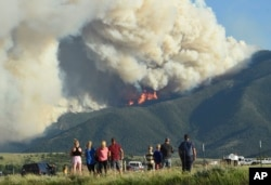 Residents watch as flames from the Robertson Draw fire burn above Red Lodge, Mont., Tuesday evening, June 15, 2021.(Larry Mayer/The Billings Gazette via AP)