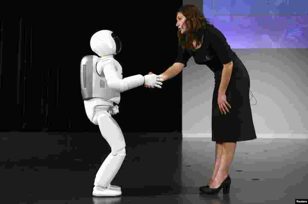 Honda's latest version of the Asimo humanoid robot shakes hands during a presentation in Zaventem near Brussels, Belgium. Honda introduced an improved version of its Asimo humanoid robot that it says has enhanced intelligence and hand dexterity, and is able to run at a speed of some 9 kilometers per hour (5.6 miles per hour).