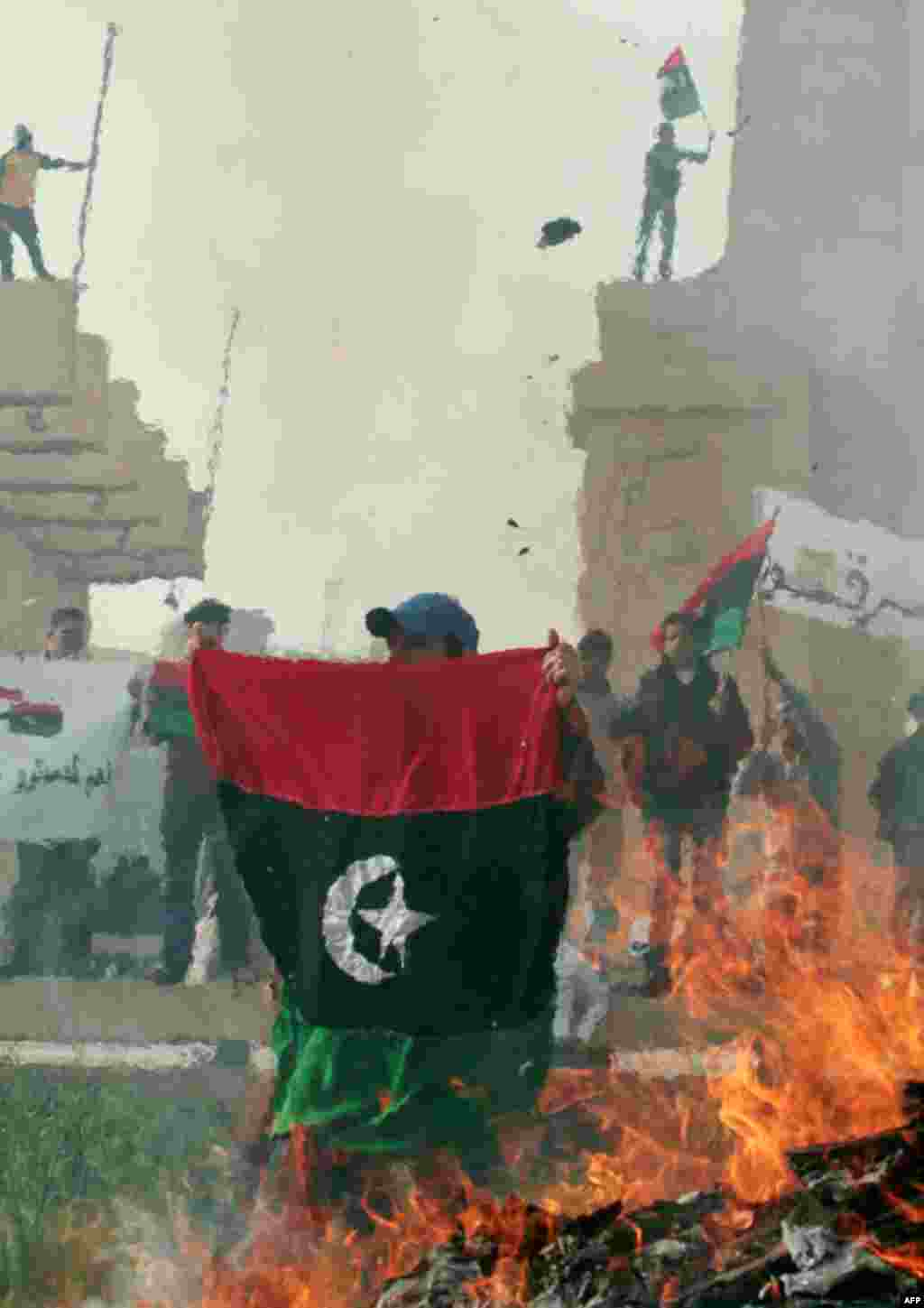 Protesters burn pictures of Gaddafi and copies of the Green Book. (Reuters/Suhaib Salem)
