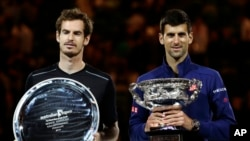 Novak Djokovic, right, of Serbia holds his trophy after defeating Andy Murray, left, of Britain in the men's singles final at the Australian Open tennis championships in Melbourne, Jan. 31, 2016.