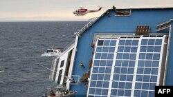 Spasioci se penju po strmoj palubi prevrnutog italijanskog broda Kosta Konkordija, nasukanog kraj italijanske obale