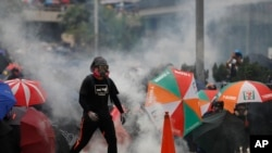 Polisi menembakkan gas air mata setelah demonstran menolak perintah untuk membubarkan diri dalam aksi protes di Hong Kong, Minggu (29/9).