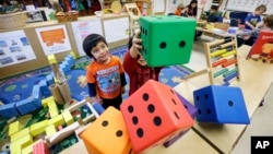 FILE - Children play with large blocks at the Creative Kids Learning Center in Seattle, Feb. 12, 2016. A lack of child care keeps many women out of work, according to the World Economic Forum.