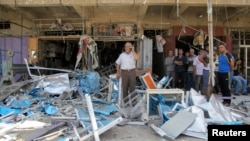 Residents stand among debris at one of the scenes of car bomb attacks that struck three mainly Shi'ite districts in Iraq's capital, Baghdad, July 19, 2014. A suicide bomber struck earlier in the day.