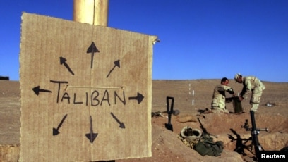 FILE - US Marines fill sandbags on the frontlines of a US Marine Corps base, near a cardboard sign reminding everyone that Taliban forces could be anywhere, in southern Afghanistan, Dec.  1, 2001.