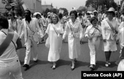 Dick Gregory, left, marches for equal rights for women.