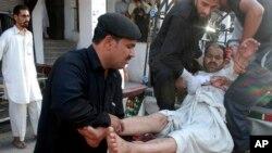Seorang korban luka-luka akibat ledakan bom di sebuah masjid di Malakand, Khyber Pakhtunkhwa, sebelum dilarikan ke rumah sakit di Peshawar, Pakistan (17/5).