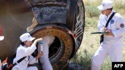 Các nhân viên thu nhặt một mẫu từ phi thuyền Thần Châu-9 sau khi phi thuyền đáp xuống