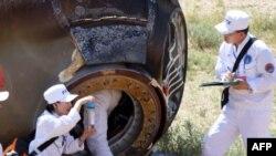 回收小组成员2012年6月29日在中国北部的边远地区收集表面烧焦的神舟九号返回舱的一个样本