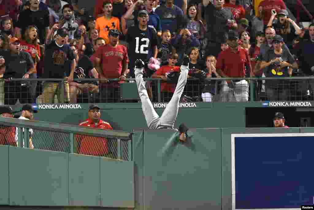 កីឡាករនៃមជ្ឈមណ្ឌល Cleveland Indians លោក Austin Jackson អាយុ២៦ឆ្នាំធ្លាក់ពីជញ្ជាំងបន្ទាប់ពីព្យាយាមឆក់បាល់ពី Hanley Ramirez (មិននៅក្នុងរូបភាព) នៃក្រុម Boston Red Soxក្នុងការប្រកួតជុំទី០៥ នៅក្នុងកីឡដ្ឋាន Fenway Park ទីក្រុង Boston រដ្ឋ Massachusetts។