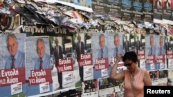 A woman walks past pre-election posters in Athens June 16, 2012. Greece holds general parliamentary elections on June 17.