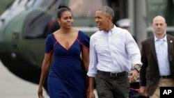 Presiden AS Barack Obama dan ibu negara Michelle Obama di bandar udara Matha's Vineyard di West Tisbury, Massachusetts (6/8). (AP/Manuel Balce Ceneta)