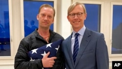 FILE - In this image provided by the U.S. State Department, Michael White holds an American flag as he poses for a photo June 4, 2020, with U.S. special envoy for Iran Brian Hook at the Zurich, Switzerland, airport after White's release from Iran.