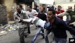 埃及人在开罗抬着在警民冲突中受伤者