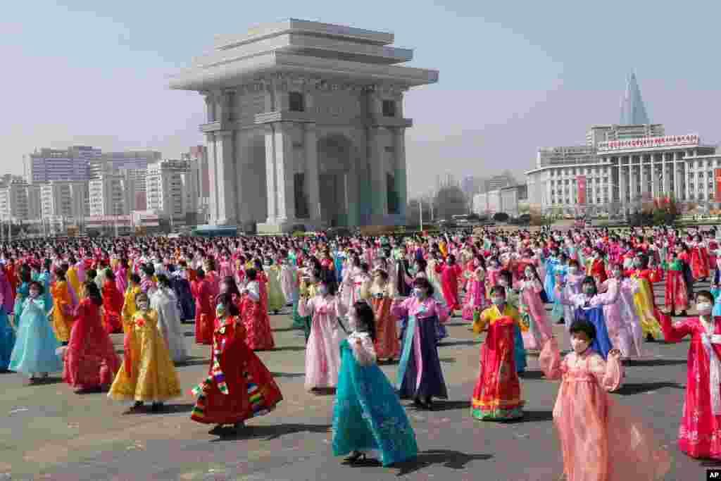 Mulheres dançam perto do Arco do Triunfo no Dia do Sol, aniversário de nascimento do falecido líder Kim Il Sung, em Pyongyang, Coreia do Norte, 15 de Abril de 2021. (AP Photo / Jon Chol Jin)