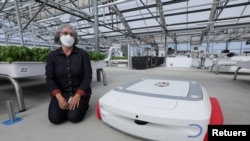 Sarah Osentoski, Senior Vice President of Engineering at Iron Ox, kneels next to the Autonomous Robot Grover in the Silicon Valley Company Greenhouse in Gilroy, California, United States, September 15, 2021. REUTERS / Nathan Frandino