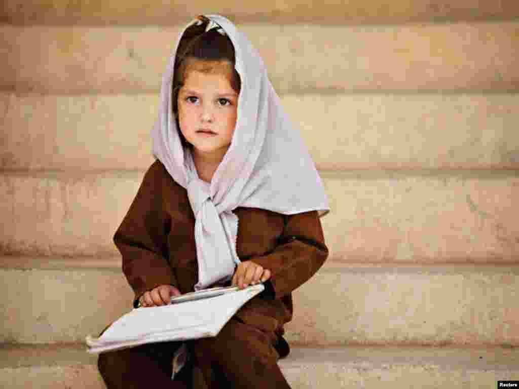 افغانستان کے شہر قندھار ایئر فیلڈ کے قریب کینیڈین فوجیوں کی جانب سے بنائے گئے سید پاشا اسکول میں زیر تعلیم معصوم بچی کلاس کے باہر بیٹھی ہے۔
