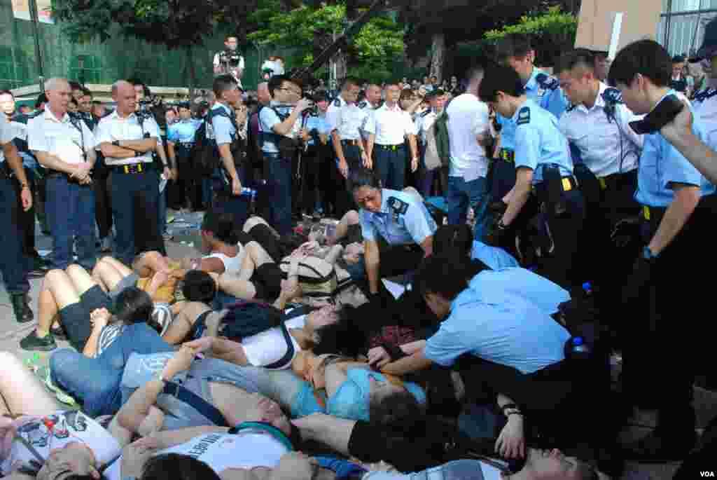 中環遮打道上預演佔中靜坐人士手扣手、躺在地上,盡量拖延警方清場時間