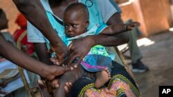 FILE - In this Wednesday, Dec. 11, 2019 file photo, a baby from the Malawi village of Tomali is injected with the world's first vaccine against malaria in a pilot program. WHO recommended the vaccine to curb the spread of the parasitic disease. (AP Photo/Jerome Delay, file)