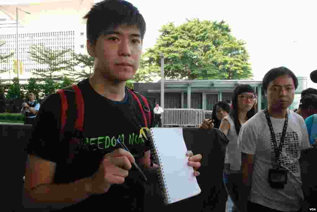香港學聯副秘書長岑敖暉展示準備交給特首梁振英的一本筆記簿及一枝筆